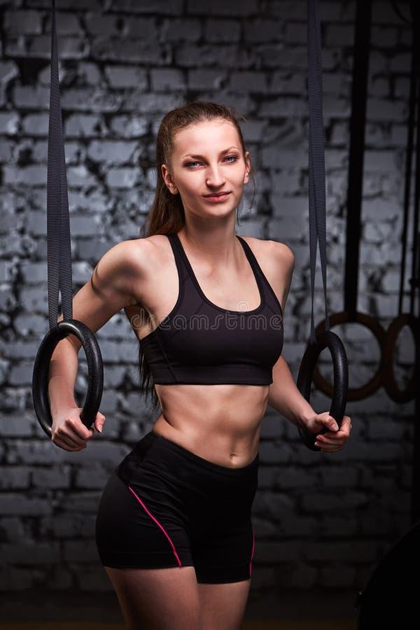 Immagine di bella giovane donna sportiva nello sportwear nero che fa esercizio di tirata-UPS facendo uso degli anelli relativi al fotografia stock