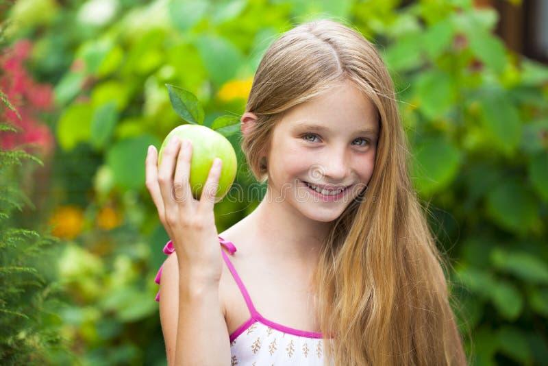 Immagine di bella ragazza con la mela verde fotografia stock