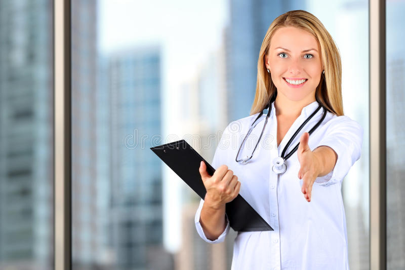 Immagine di bello medico della donna che esamina macchina fotografica e che dà una mano fotografia stock libera da diritti