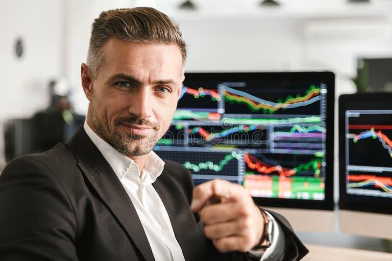 Immagine di bello uomo d'affari che lavora nell'ufficio sul computer con i grafici ed i grafici allo schermo fotografia stock