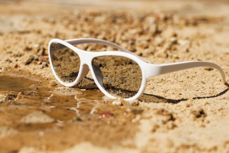 Immagine di concetto delle vacanze estive con la scena della spiaggia in occhiali da sole sulla sabbia immagini stock libere da diritti