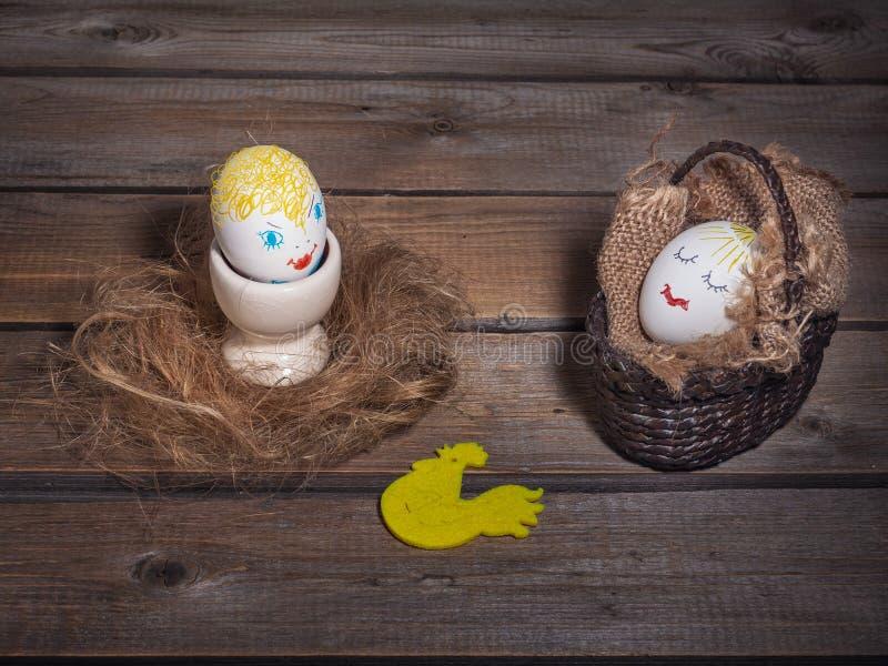 Immagine di divertimento con le uova con i fronti dipinti Uno è in un canestro di vimini e l'altro è su un supporto dell'uovo fotografia stock libera da diritti