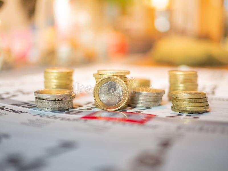 Immagine di euro pile della moneta sul calendario che indica giorno di paga fotografie stock libere da diritti