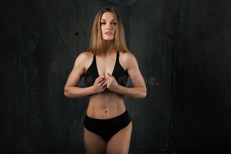 Immagine di giovane atleta femminile muscolare che indossa usura nera di sport che sta guardante in camera sul fondo scuro Cultur immagine stock libera da diritti