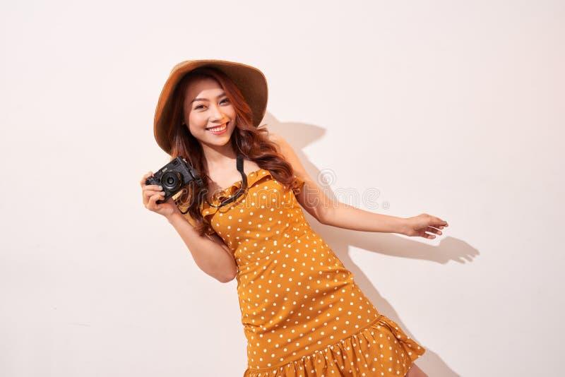 Immagine di giovane donna del fotografo isolata sopra la macchina fotografica beige della tenuta della parete del fondo fotografia stock libera da diritti