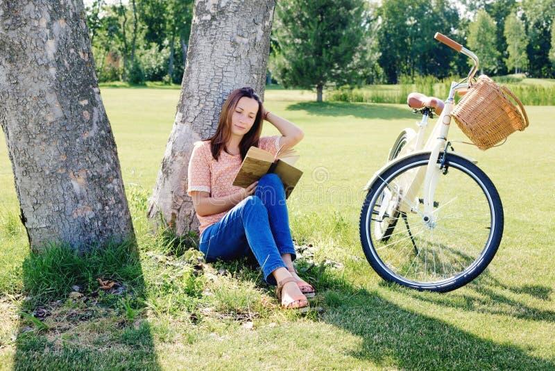 Immagine di giovane donna felice che si siede sotto l'albero con il libro immagini stock libere da diritti