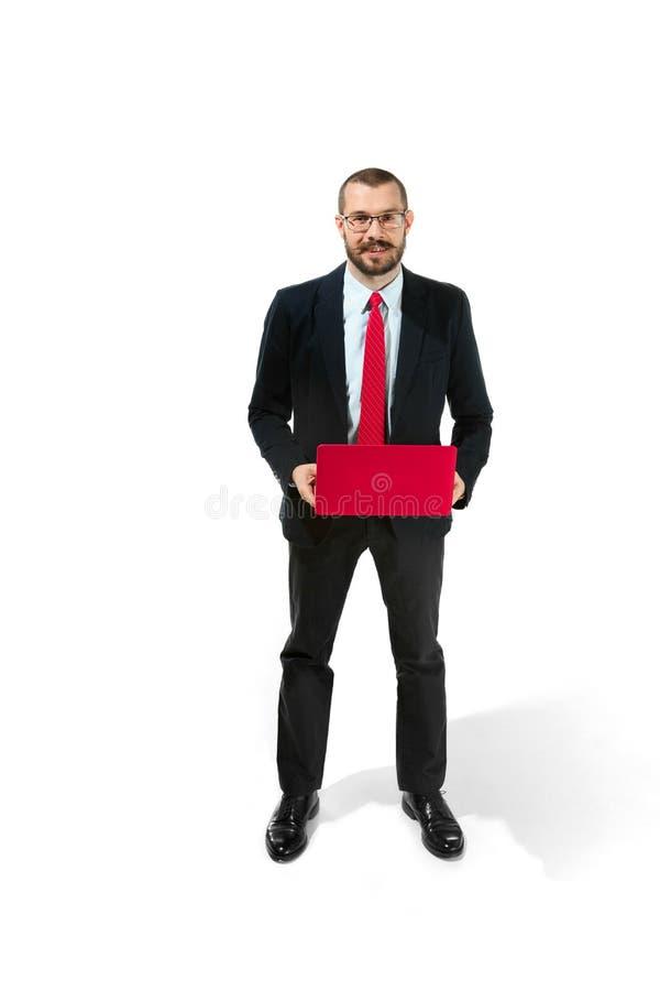Immagine di giovane uomo barbuto bello che controlla il fondo bianco dello studio con il computer portatile fotografie stock libere da diritti