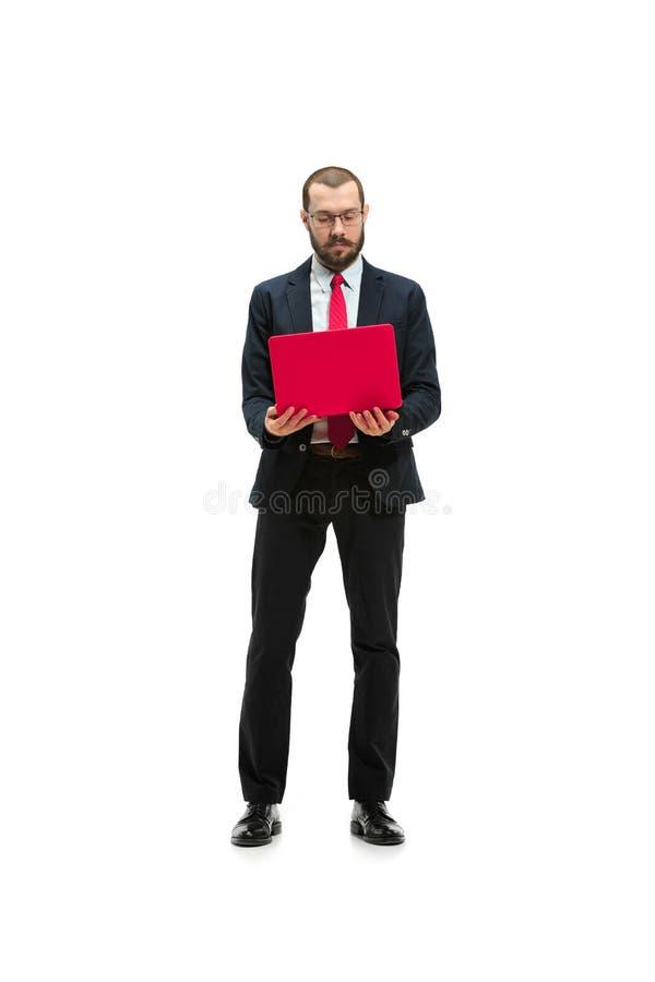 Immagine di giovane uomo barbuto bello che controlla il fondo bianco dello studio con il computer portatile immagini stock libere da diritti