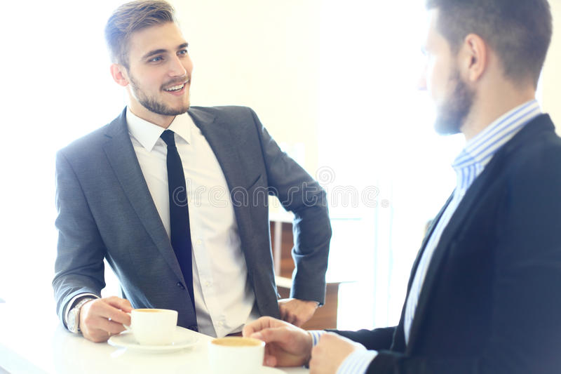 Immagine di giovane uomo d'affari con la tazza di caffè che comunica con il suo collega immagine stock