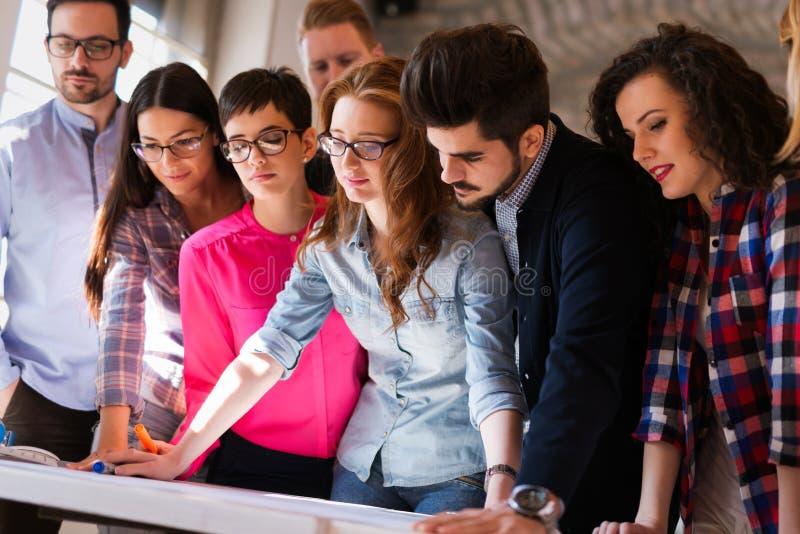 Immagine di giovani architetti che discutono nell'ufficio fotografia stock
