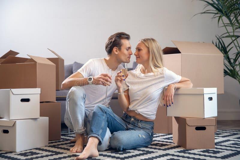 Immagine di giovani coppie con i vetri del champagne che si siedono fra le scatole di cartone fotografia stock libera da diritti