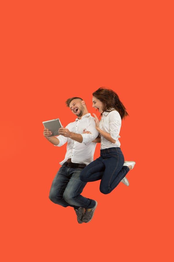 Immagine di giovani coppie sopra fondo rosso facendo uso dell'aggeggio della compressa o del computer portatile mentre saltando fotografia stock