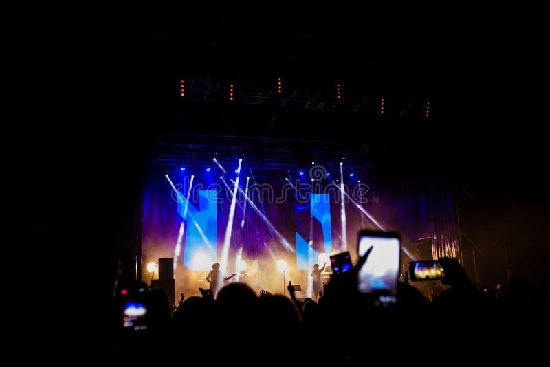 Immagine di molta gente che gode della prestazione di notte, di grande folla irriconoscibile che ballano con le mani sopra su sol fotografia stock libera da diritti