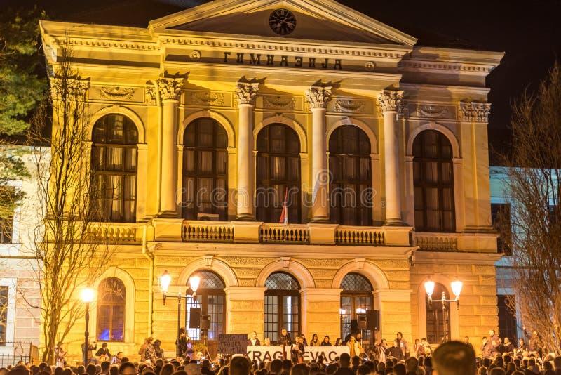 Immagine di notte della prima scuola della palestra di Kragujevac con la folla della gente che protesta contro la politica fotografie stock