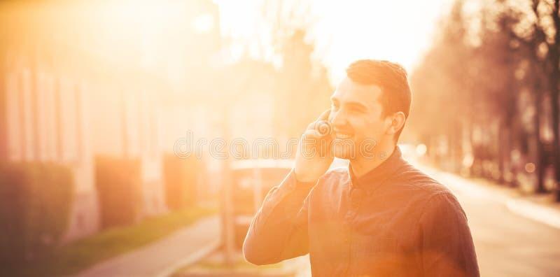 Immagine di Oned dell'uomo bello felice che parla sopra il telefono immagine stock libera da diritti