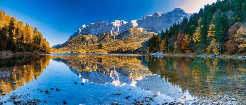 Immagine di panorama delle montagne con la riflessione dell'acqua nel lago fotografia stock