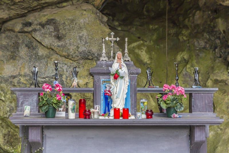 Immagine di piccola cappella in una grotta naturale con la statuetta del vergine di Lourdes fotografia stock libera da diritti