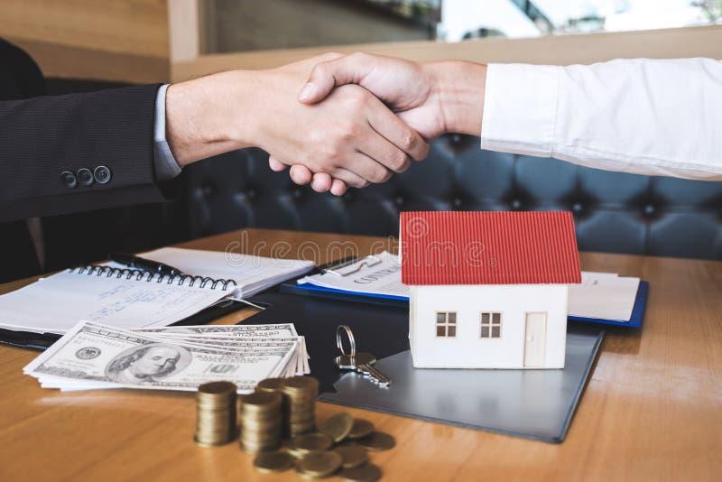 Immagine di riuscito affare del bene immobile, del mediatore e del cliente stringere le mani dopo la firma del modulo di domanda  fotografia stock