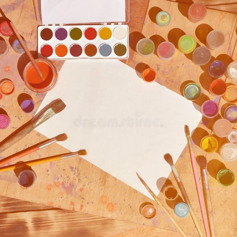 Immagine di sfondo che mostra interesse nella pittura e nell'arte dell'acquerello Un foglio bianco di carta, circondato dalle spa immagine stock