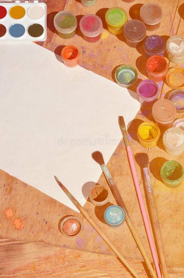 Immagine di sfondo che mostra interesse nella pittura e nell'arte dell'acquerello Un foglio bianco di carta, circondato dalle spa fotografie stock