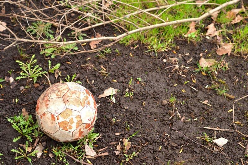 Immagine di sfondo semplice della foto di vecchia palla di calcio sulla terra fotografia stock libera da diritti