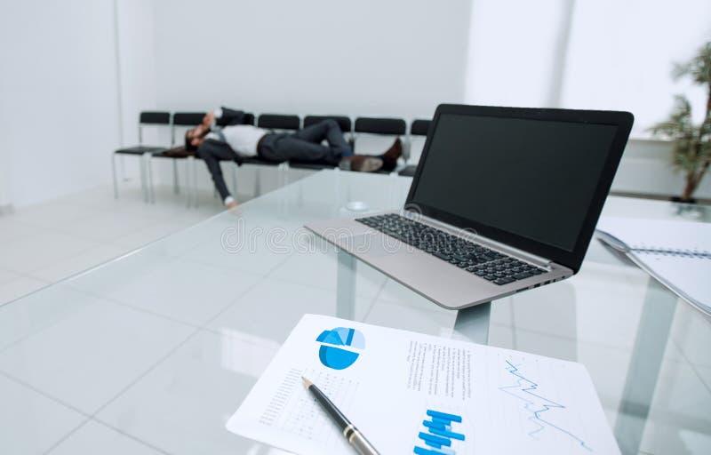 Immagine di sfondo di un computer portatile su una tavola di vetro in un ufficio vuoto immagine stock