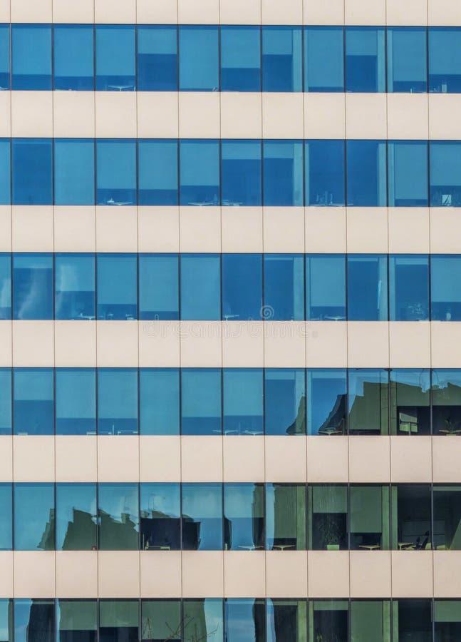 Immagine di specchio nel vetro di un edificio per uffici immagine stock