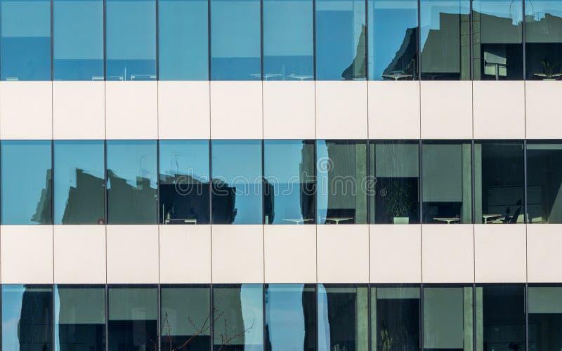 Immagine di specchio nel vetro di un edificio per uffici fotografia stock