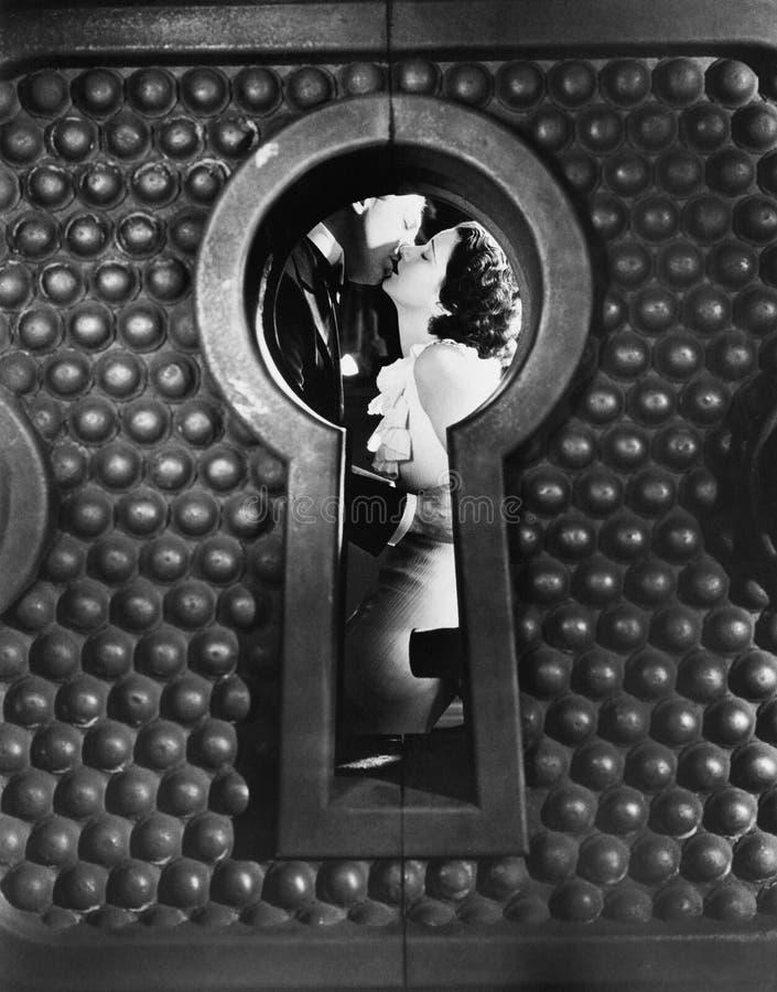 Immagine di un baciare delle coppie osservato attraverso un buco della serratura (tutte le persone rappresentate non sono vivente immagine stock