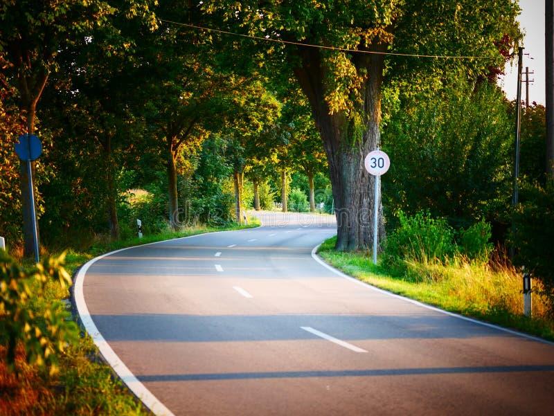 Immagine di un limite di velocità di kmh 30 accanto ad una strada curvy fotografie stock