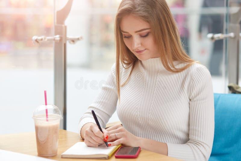 Immagine di un modello ispirato e attraente che scrive sul suo taccuino, trascorrendo del tempo da sola al bar, con smartphone e  fotografie stock libere da diritti