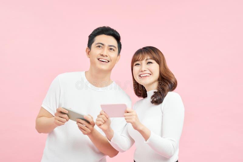 Immagine di una coppia eccitata uomo e donna che sorride mentre entrambi usano telefoni isolati su sfondo rosa immagine stock