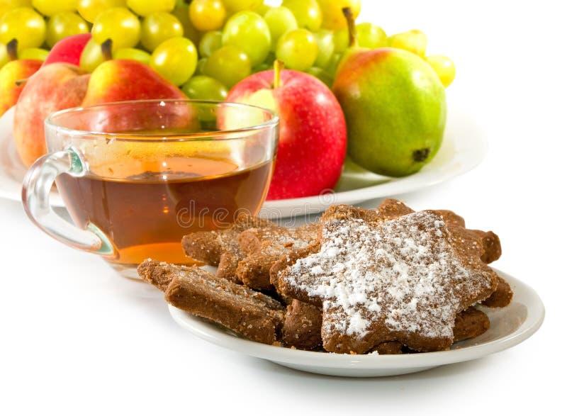 Immagine di una tazza di tè, dei biscotti e della frutta immagine stock libera da diritti