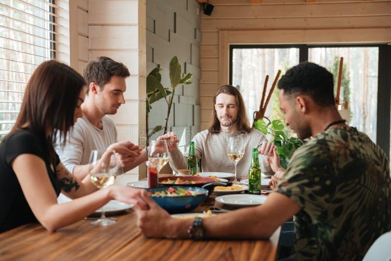 Immagine di vista laterale di un gruppo di amici che pregano su tavola di cena fotografie stock
