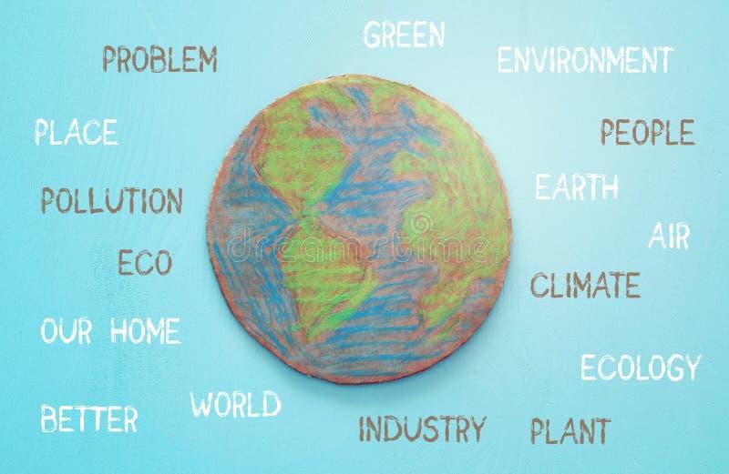 Immagine di vista superiore del globo della terra del cartone con testo ambientale sopra fondo di legno blu fotografia stock libera da diritti