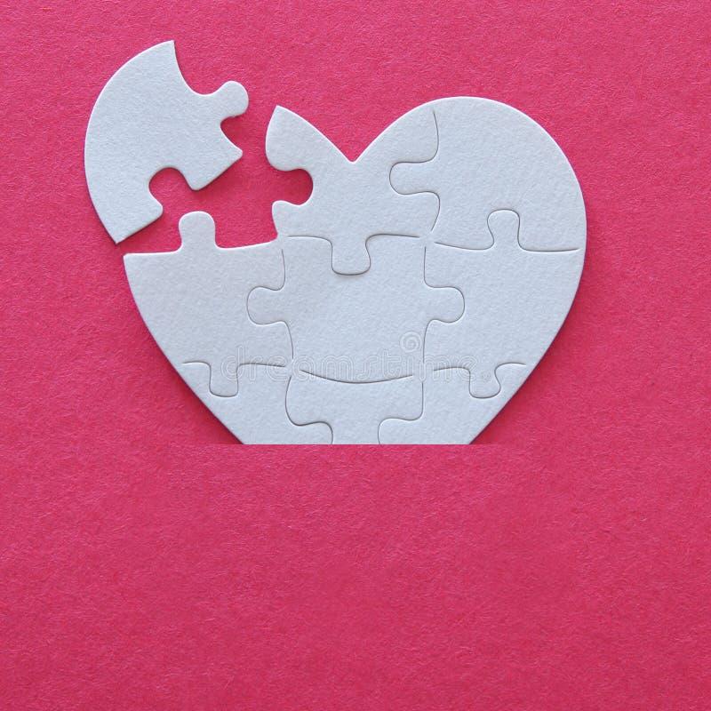 Immagine di vista superiore del puzzle bianco di carta del cuore con il pezzo mancante sopra fondo rosa La sanità, dona, il giorn fotografia stock