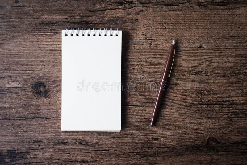 Immagine di vista superiore del taccuino aperto con la pagina in bianco e della penna su w fotografie stock