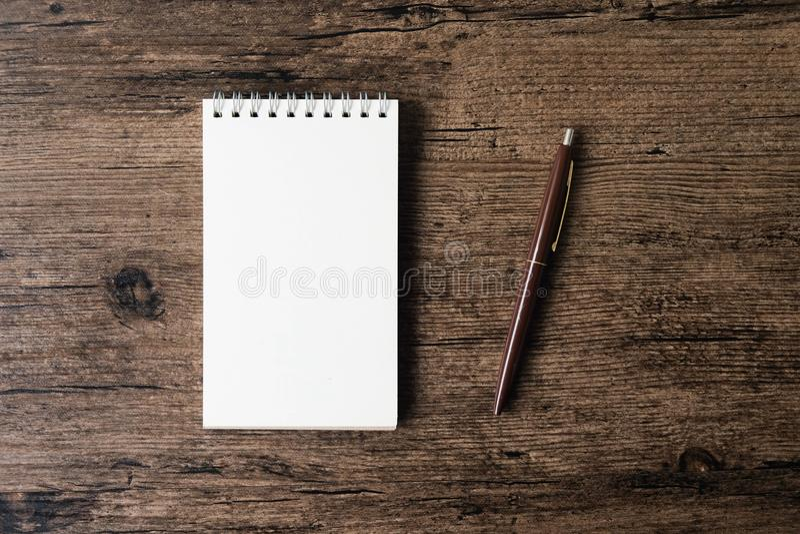 Immagine di vista superiore del taccuino aperto con la pagina in bianco e della penna su w immagine stock libera da diritti