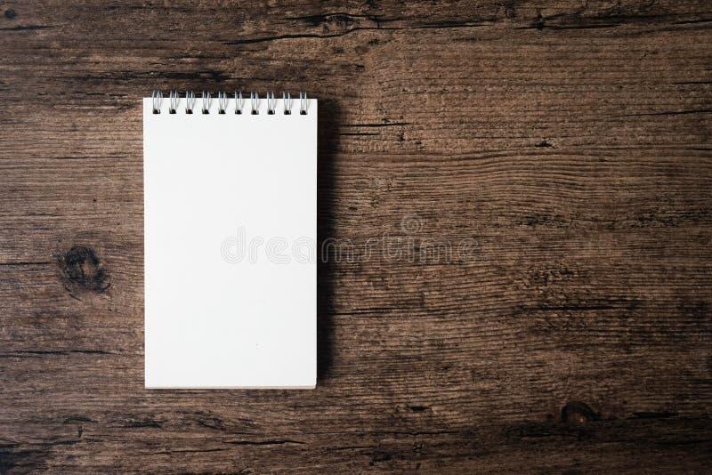 Immagine di vista superiore del taccuino aperto con la pagina in bianco sui tum di legno immagine stock libera da diritti