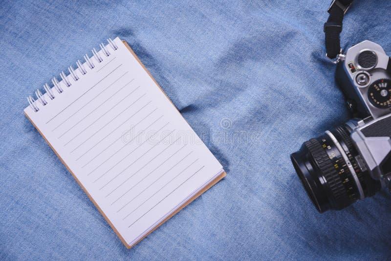 immagine di vista superiore del taccuino aperto con le pagine in bianco e della macchina fotografica su blackground blu immagine stock