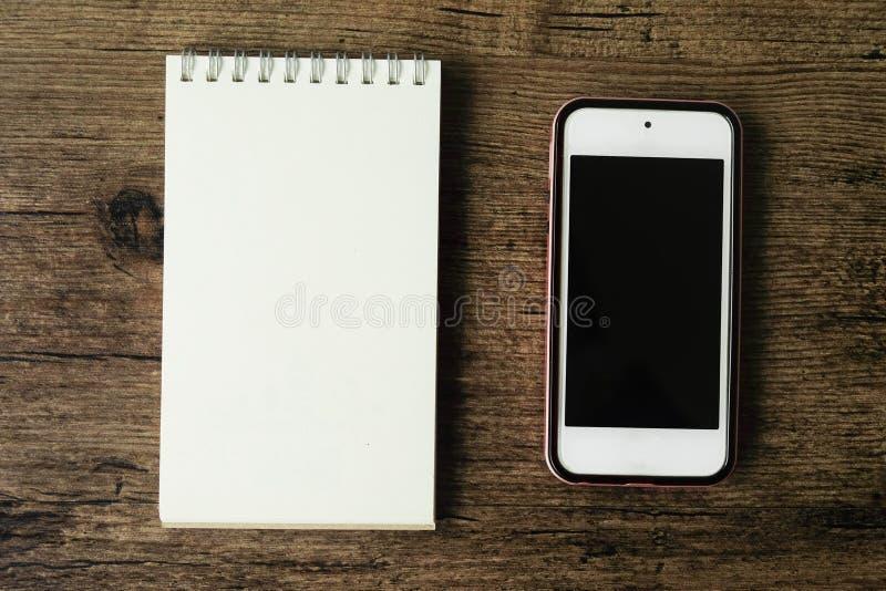 Immagine di vista superiore del taccuino della pagina in bianco con lo Smart Phone sul wo fotografie stock libere da diritti