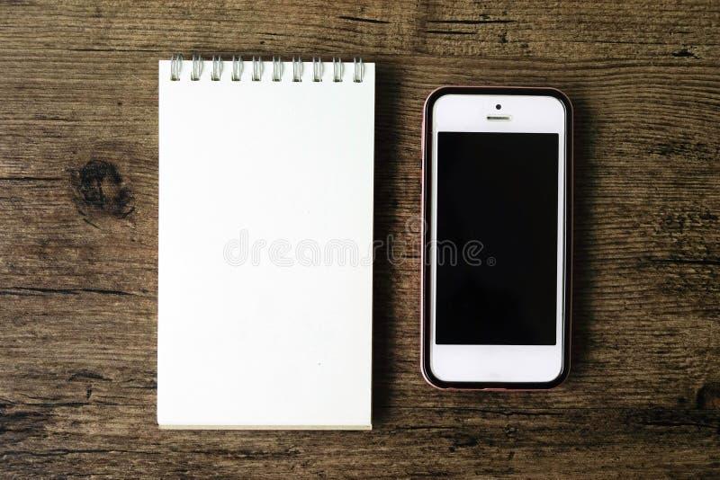 Immagine di vista superiore del taccuino della pagina in bianco con lo Smart Phone sul wo fotografia stock libera da diritti