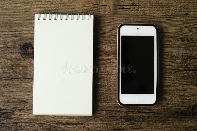 Immagine di vista superiore del taccuino della pagina in bianco con lo Smart Phone sul wo immagini stock