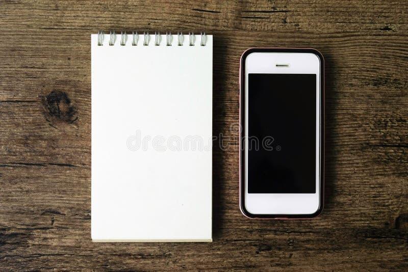 Immagine di vista superiore del taccuino della pagina in bianco con lo Smart Phone sul wo fotografia stock