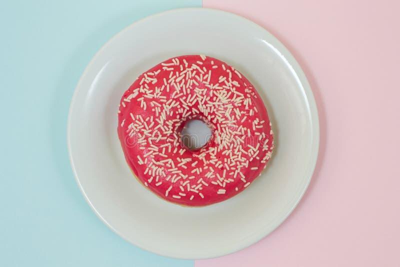 Immagine di vista superiore della ciambella rosa dolce saporita sul piatto bianco dentro immagine stock