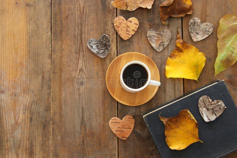 Immagine di vista superiore della tazza di caffè sopra le foglie di autunno di legno e asciutte e della pila di libro immagini stock