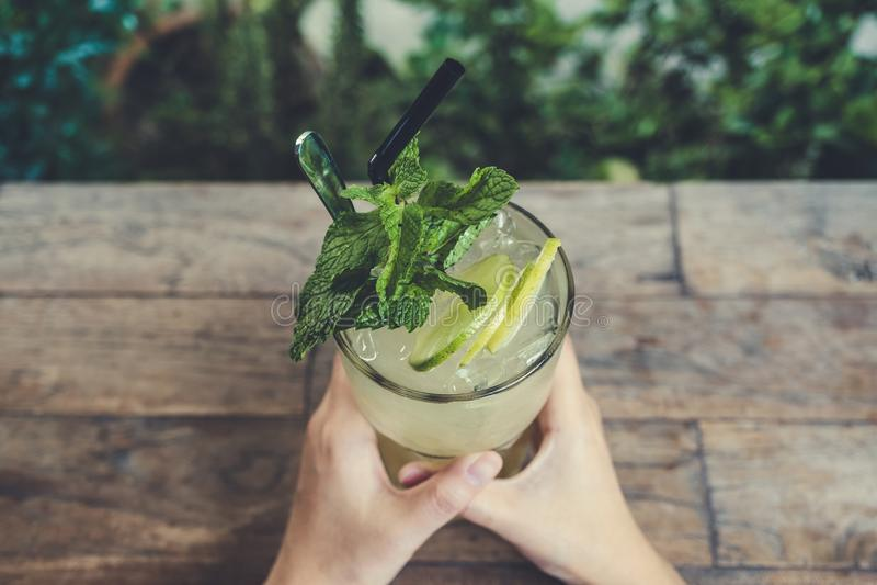 Immagine di vista superiore delle mani che tengono un vetro del succo di limone ghiacciato con le foglie di menta fotografia stock