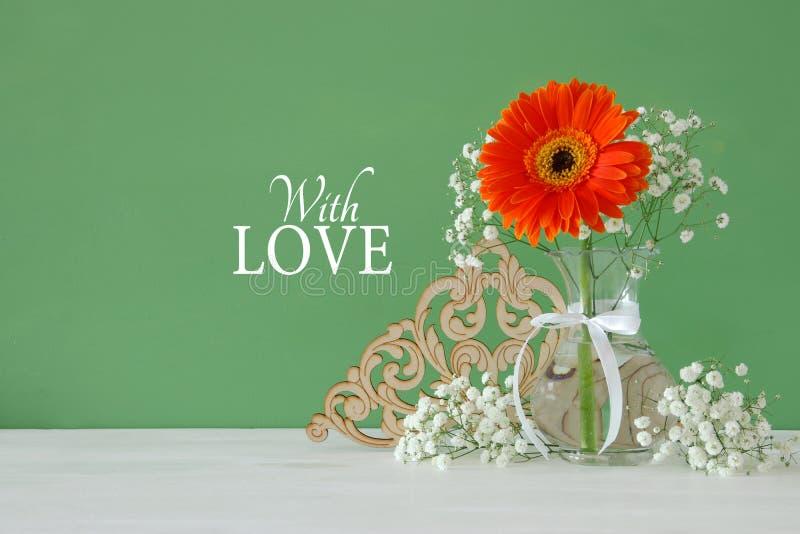 Immagine di women& internazionale x27; concetto di giorno di s con il bello fiore nel vaso sulla tavola di legno immagini stock libere da diritti