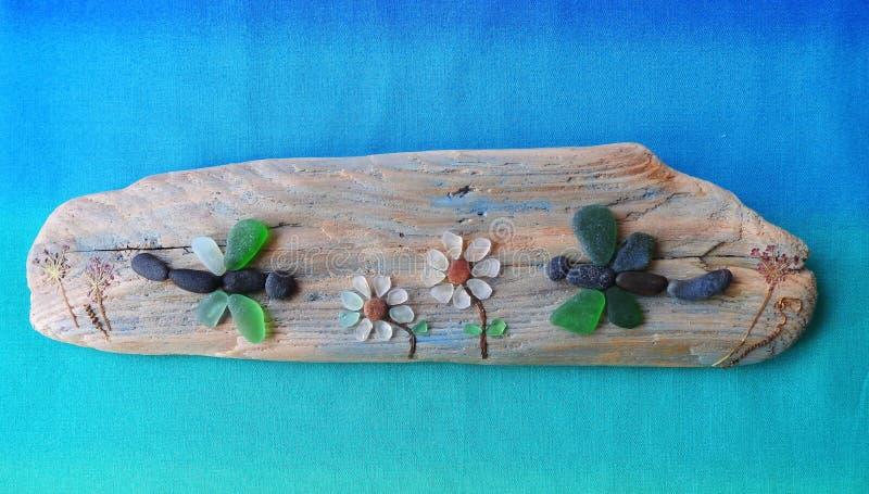 Immagine fatta a mano - libellula e fiori su superficie di legno, Lituania immagine stock