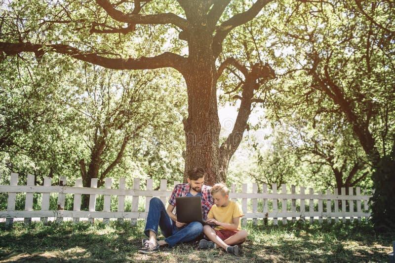 Immagine fresca del padre e del figlio che si siedono insieme sotto il grande ed albero verde Stanno esaminando lo schermo del `  fotografia stock libera da diritti